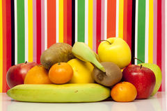 frukter Apple päron, apelsin, grapefrukt, mandarin, kiwi, banan Mång--färg bakgrund Arkivfoton