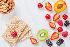 Frukter, bär och knaprigt bröd för helt korn på utrymme för kopia för vitmarmortabell äta för begrepp som är sunt fotografering för bildbyråer