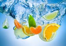 Frukter faller djupt under vatten med en stor färgstänk Fotografering för Bildbyråer