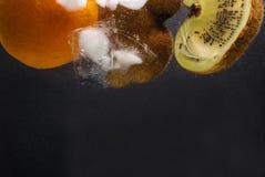 Frukter med is i vatten arkivbilder