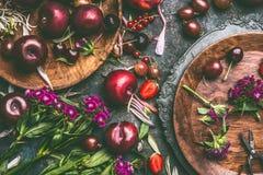 Frukter och bär för sommar säsongsbetonade med trädgårds- blommor i plattor på mörk lantlig bakgrund royaltyfri bild