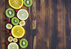 Frukter och bär kiwi, citron, banan, hallon, vinbär, apelsin på träbakgrund Royaltyfri Fotografi