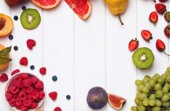 Frukter och bär på den vita träbakgrunden Royaltyfria Bilder