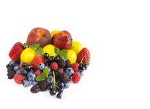Frukter och bär på vit bakgrund Mogna vinbär, jordgubbar, björnbär, blåbär, hallon, persikor och Arkivfoton