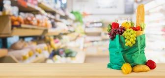 Frukter och grönsaker i shoppingpåse på trätabellöverkant med supermarketlivsmedelsbutiken royaltyfri bild