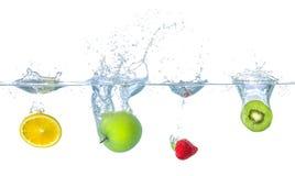 Frukter som faller in i vatten med färgstänk Fotografering för Bildbyråer