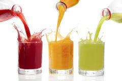 Fruktfruktsafter hällde från flaskor kiwin, vinbär, apelsin Fotografering för Bildbyråer