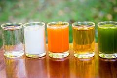 Fruktfruktsafter, orange fruktsaft, äppelmust, kiwifruitfruktsaft, med mjölkar och bevattnar i exponeringsglas arkivfoton
