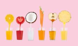 Fruktfruktsafter som flödar från nya frukter på bakgrund för pastellfärgade rosa färger royaltyfri foto