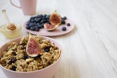 Fruktgranola i den rosa bunken, blåbär, fikonträd och honung på en vit träbakgrund, sidosikt kopiera avst?nd royaltyfri foto