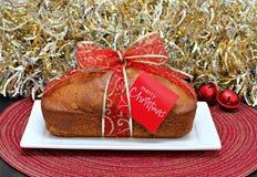 Fruktkaka med ett julband och en glad julkort Arkivfoton