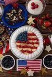 Fruktkaka och olika söta foods som är ordnade på trätabellen Arkivfoton
