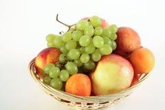 Fruktkorg med den äpplepersikadruvan och aprikons på vit bakgrund Royaltyfri Foto