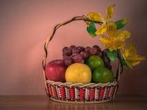 Fruktkorg på trätabellen med konkret bakgrund för vägg, Sti royaltyfri bild