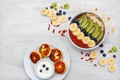 Fruktmousse i bunkar för den nya organiska smoothien för sund frukost som göras från bananen, kiwi, spirulina, wheatgrass och royaltyfri foto