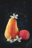 Fruktpäron och vitpersika med små blommor av Apple på ett träbrädeslut upp i bottenlägetangentcloseup royaltyfri bild