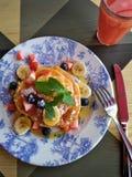 Fruktpannkakor och smoothie för sund frukost arkivbild