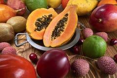 Fruktpapaya på en metallplatta, runt om många frukter av olik art fotografering för bildbyråer