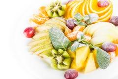 Fruktplatta, äpple mandarin, kiwi, druvor, mintkaramell, päron, äpple, ananas Fruktsallad i plattanärbild Fotografering för Bildbyråer