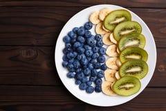 Fruktplatta Blåbär-, banan- och kiwiskivor på en platta, fla Royaltyfri Bild
