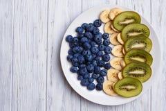 Fruktplatta Blåbär-, banan- och kiwiskivor på en platta, fla Royaltyfria Bilder