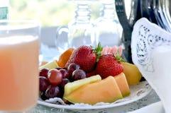 Fruktplatta med fruktsaft på säng - och - frukost Royaltyfria Foton