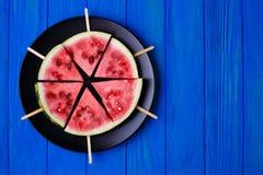 Fruktplatta Vattenmelonskivapopslices på en platta på blå woode Royaltyfri Foto