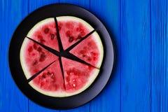 Fruktplatta Vattenmelonskivor på en svart platta på blått träb Arkivbild