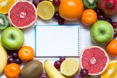 Fruktrambakgrund och anmärkning med bananen, kiwi, äpple, citron på den vita trätabellen, sunt matbegrepp arkivbild