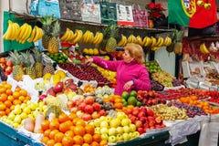 Fruktsäljareuppläggning och taomsorg av ställningen i inre av den historiska Bolhao marknaden Royaltyfri Bild