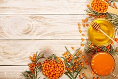 Fruktsaft eller te för havsbuckthorn med honung på en vit träbakgrund med kopieringsutrymme för din text Top beskådar royaltyfri fotografi
