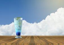 Fruktsaft för italiensk sodavatten för med is blått ny på den tomma wood tabellen och härlig blå himmel och moln i bakgrund nytt  Royaltyfria Foton