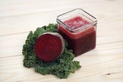 Fruktsaft för röd beta i ett exponeringsglas med betahalvor och ett blad av grönkål på en ljus bakgrund Arkivfoto