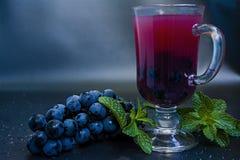 Fruktsaft för röd druva i exponeringsglas- och druvafrukter som isoleras på mörk bakgrund royaltyfri bild