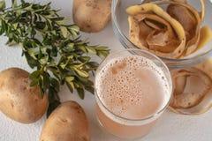 Fruktsaft i ett exponeringsglas med potatisar vitt arbete för bakgrundspotatisstudio arkivfoton