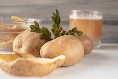 Fruktsaft med potatisar i ett exponeringsglas skalade potatisar fotografering för bildbyråer