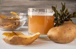 Fruktsaft med potatisar i ett exponeringsglas skalade potatisar royaltyfria foton