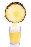 Fruktsaft som hälls in i ett exponeringsglas av ananas Royaltyfria Foton