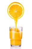 Fruktsaft som hälls in i ett exponeringsglas av apelsinen Arkivbild