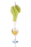 Fruktsaft som hälls in i ett exponeringsglas av druvor Arkivfoto