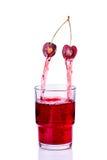 Fruktsaft som hälls in i ett exponeringsglas av körsbäret Royaltyfri Fotografi