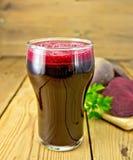 Fruktsaftbeta i högväxt exponeringsglas ombord Arkivfoto