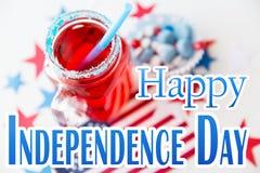Fruktsaftexponeringsglas och amerikanska flaggan på självständighetsdagen Arkivfoton