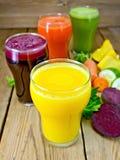 Fruktsaftgrönsak i fyra exponeringsglas ombord Arkivfoton
