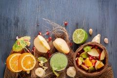 Fruktsallad av äpplen, bananer, apelsinen och granatäpplet i halva en kokosnöt och nya gröna smoothies från grönsaker, limefrukt  Arkivfoto