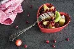 Fruktsallad i hjärtaformbunke fotografering för bildbyråer