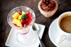 Fruktsallad med gelépudding i exponeringsglas och kaffe i den vita koppen royaltyfri fotografi