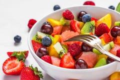Fruktsallad med vattenmelon, jordgubben, k?rsb?ret, bl?b?ret, kiwin, hallonet och persikor i en bunke med gaffeln arkivbilder