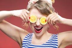 Fruktserie Stående av att le passionerat Caucasian blont posera med citroner Arkivfoto