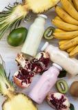 Fruktsmoothies av olika f?rger i exponeringsglaskrus med ingredienser p? vit tr?yttersida Lekmanna- l?genhet Fr?n ?ver b?sta sikt arkivfoto